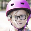 Child with pink bicycle helmet and black glasses — Stock Photo #53215063
