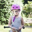 Child with pink bicycle helmet and black glasses on bike — Stock Photo #53215563