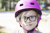 Child with pink bicycle helmet and black glasses — 图库照片
