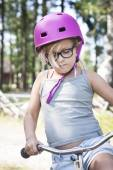 Girl with pink helmet, black glasses and bicycle — Zdjęcie stockowe