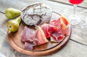 Slices of italian ham on the wooden board — Stock Photo