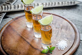 Glasses of tequila on the wooden board — Stock Photo