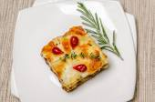 Portion of lasagna on the square plate — Stock Photo