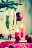 Glasses of champagne under decorated christmas tree branch — Stock Photo