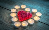 Heart with burning candles on the wooden background — Stock Photo