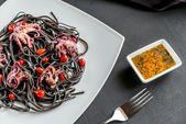 Pasta with black cuttlefish ink and small octopuses — Stock Photo