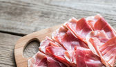 Slices of jamon on the wooden board — Stock fotografie
