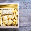 Various types of pasta in the wooden container — Stock Photo #64240589