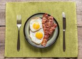 Portion of fried eggs with bacon — Stock Photo