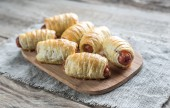 Sausage rolls on the wooden board — Stock Photo
