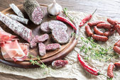 Different kinds of sausage on the wooden background — Stock Photo
