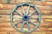 Rustic wagon wheel hanging on a wall — Stock Photo