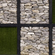 Artificial grass and stone wall as background — Stock Photo #54360805