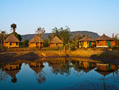 Bamboo cottages and its reflection in pond in Thailand — Stock Photo