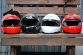 Four racing helmet are on a bench near the race track — Stock Photo