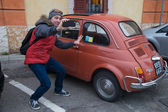 Young guy doing selphy next to a small car in Italy — Stock Photo