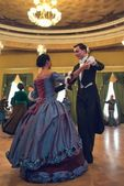 Pair in historical dress dancing a waltz in the ballroom — Stock Photo