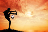 Footballer silhouette at sunset — Stock Photo