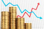 Pile of coins and chart. Success and failure of investment. — Stock Photo