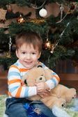 Happy little boy with a teddy bear in a Christmas tree (3 years — Stock Photo