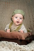 Smiling baby (3,5 months) in a cap lying in the retro-suitcase  — Stock Photo