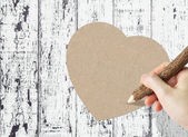 Woman hand writing paper heart on wooden background — Stock Photo