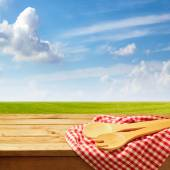 Wooden table with kitchen utensil over green meadow and blue sky — Stock Photo