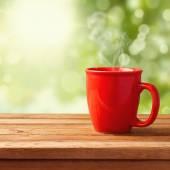 Coffee mug over garden bokeh — Photo