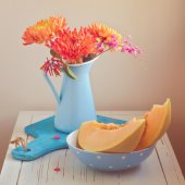 Melon and flowers on vintage table. Focus on melon. Retro filter effect — Стоковое фото