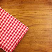 Wooden table with red checked tablecloth — Stock Photo