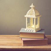 Lantern with candle and books — Stock Photo