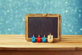 Wooden spinning top and chalkboard — Stock Photo