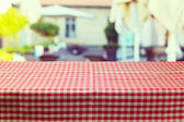 Table with red checked tablecloth — Stock Photo