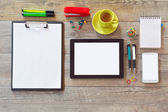 Office desk with tablet smartphone and coffee — Stock Photo