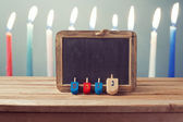 Dreidel and chalkboard over candles — Stock Photo