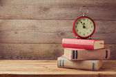 Books and clock on wooden table — Stock Photo