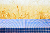 Table with tablecloth over wheat field — Foto Stock