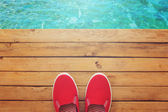 Canvas shoes on wooden deck — Stock Photo