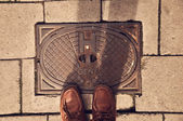 Sewer manhole with feet in shoes — Stockfoto