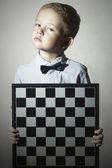 Little boy with chessboard.fashion children.Bow-tie.Little genius Child. Intelligent game.Emotion — Stok fotoğraf