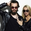 Gorgeous fashion beautiful couple in black clothes wearing trendy glasses together. Hipster boy and girl. Bearded young man and blonde in sunglasses — Stok fotoğraf #74819659
