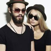 Beautiful happy couple in hat wearing trendy glasses together. Hipster boy and girl. Bearded young man and blonde in sunglasses — Stock Photo