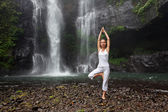 Woman meditating doing yoga between waterfalls — Stock Photo