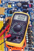 Multimeter and motherboard — Stock Photo