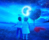 Children in the night of full moon with heart tree — Stock Photo