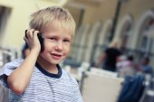Boy speaks to a mobile phone in a supermarket. — Stock Photo