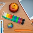 School supplies and tablet on wooden school desk from above — Stock Photo #51865177