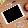 School supplies and tablet on wooden school desk from above — Stock Photo #51865797