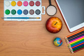 School supplies and tablet on wooden school desk from above — Stock Photo