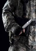 Military man with a knife in a hand close up on the black background — Stock Photo